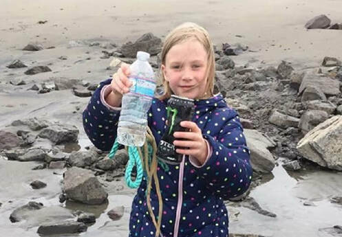 Youth holding litter removed at a beach cleanup