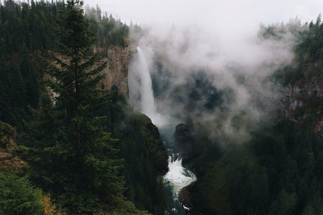 waterfall-in-mountainous-terrain-with-evergreen-forest-against-cloudy-sky