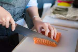 person-slicing-meat-on-white-chopping-board